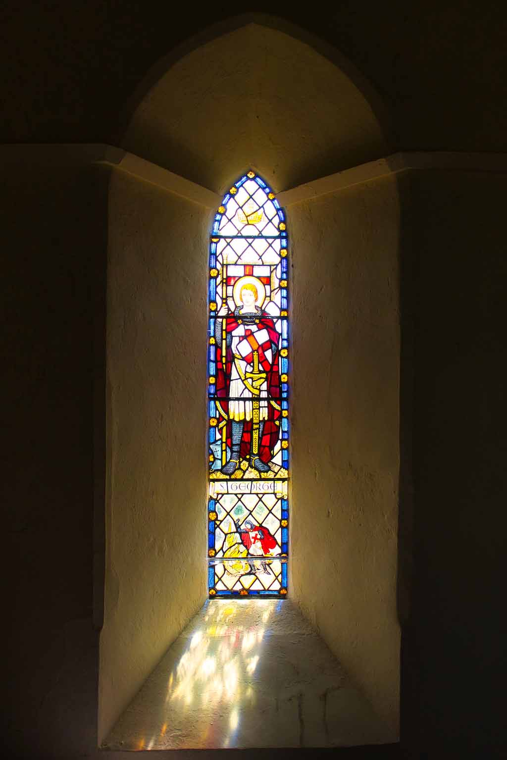 Light frolicking through a stained glass window of St George.