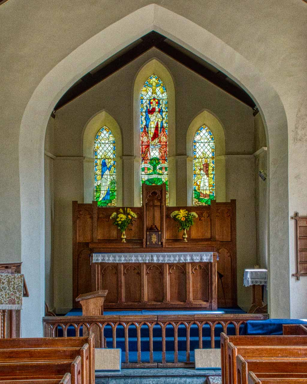The raised chancel, the altar and the stained glass were created as part of the early 20th century renovations. Glass by George Cooper Abbs.