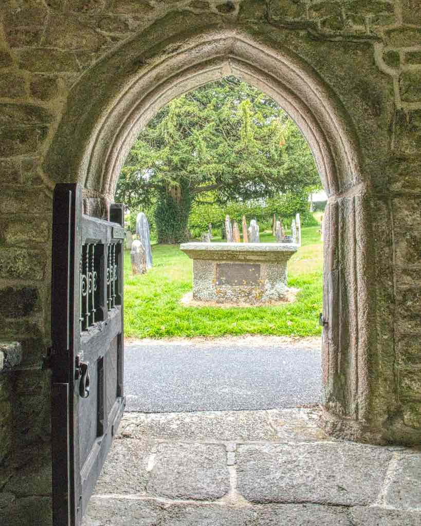 A solid porch doorway, granite rubble surrounding carved granite, looking out over a pretty churchyard.