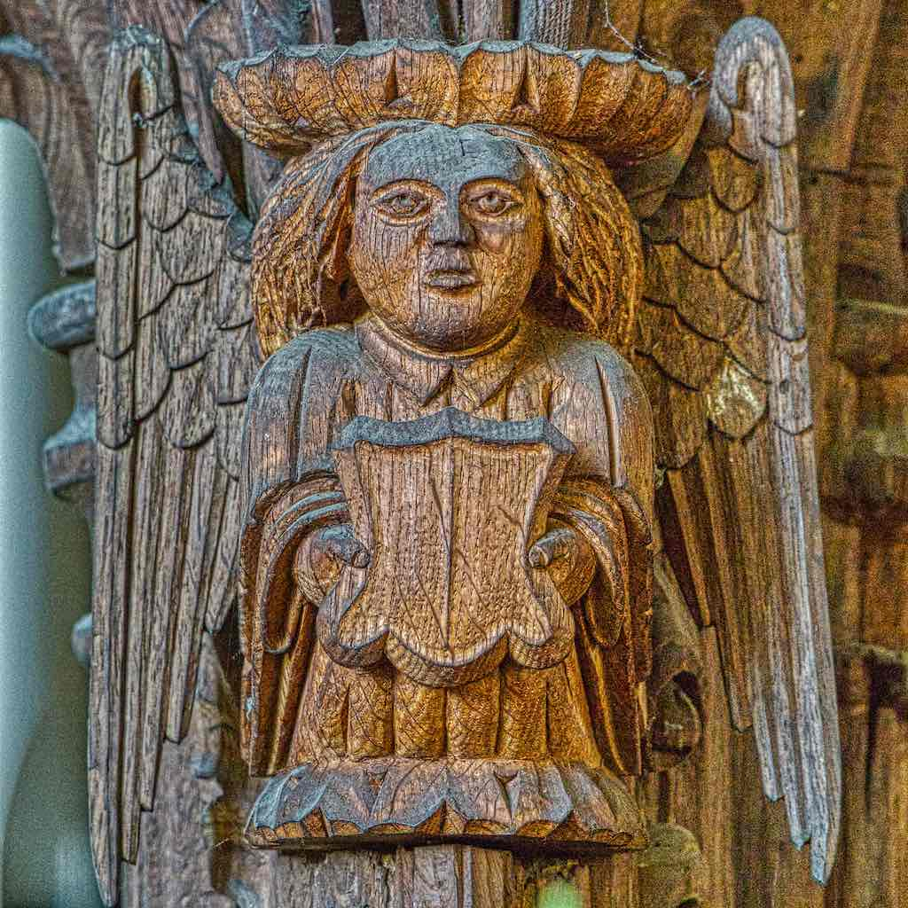 A carved angel on the 16th century roodscreen, beautifully plump, beautifully haired.