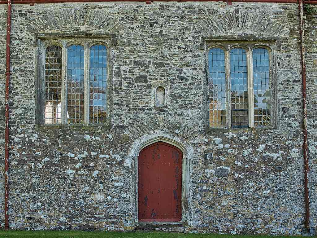 The north door with an image niche above it and 15th century windows either side.
