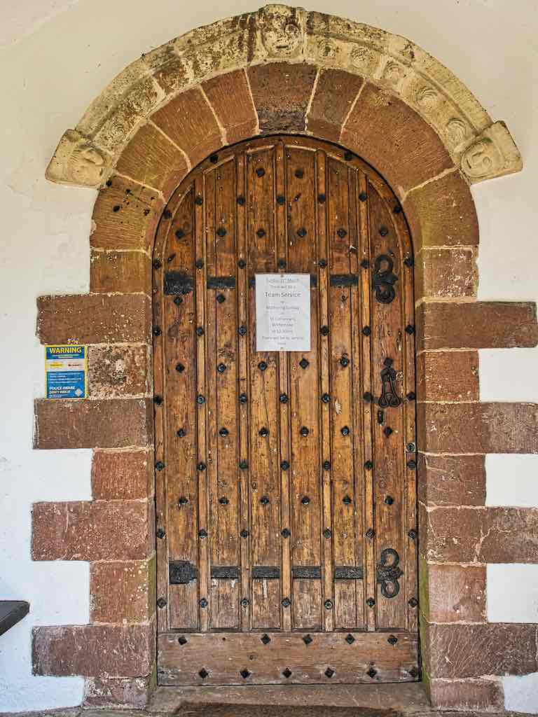 The fine south doorway with goodly Devon red stone.