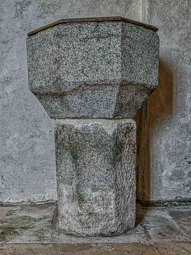 The granite font, probably from the 15th century.