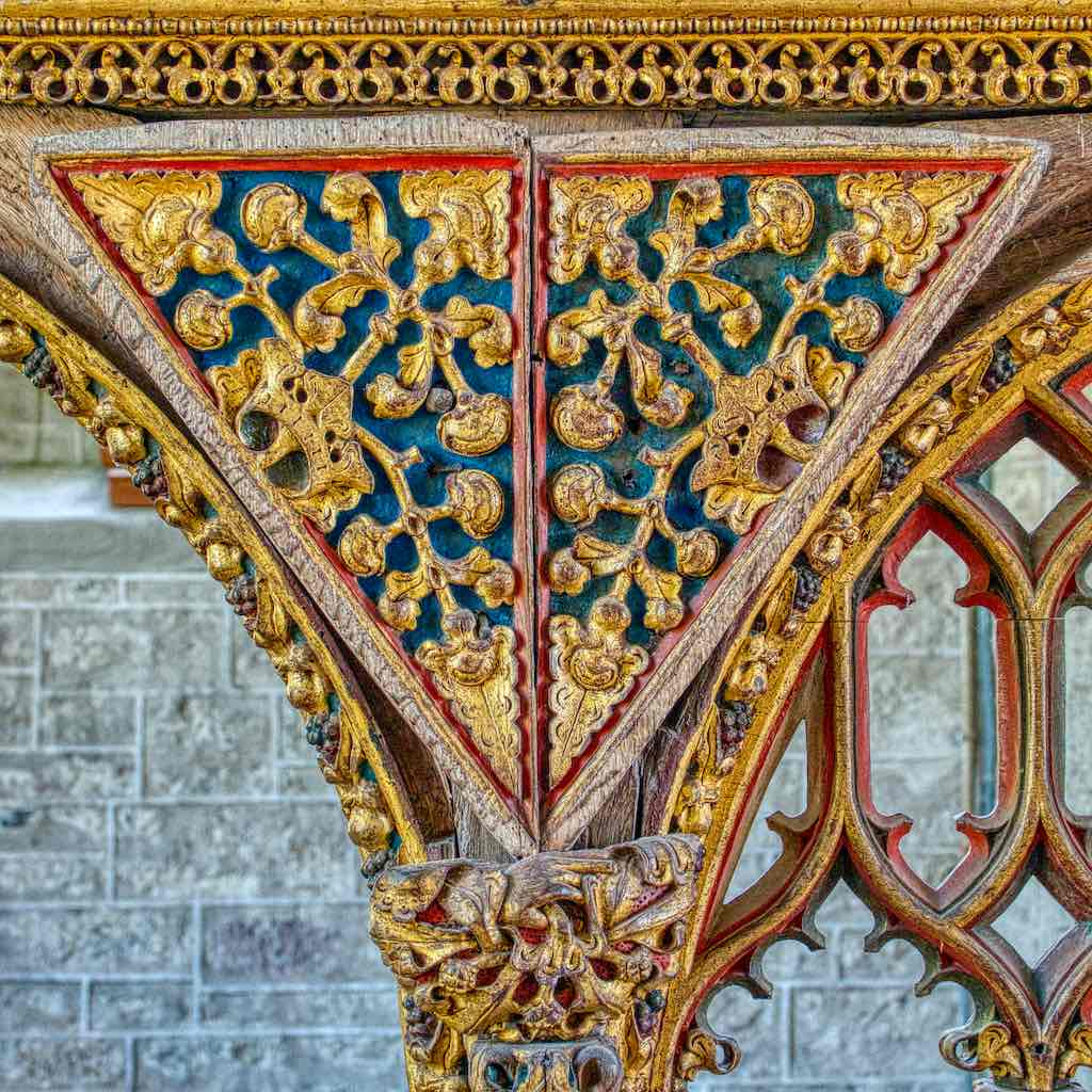 Golden seed pods growing out of crowns on the astounding rood screen in Bridford