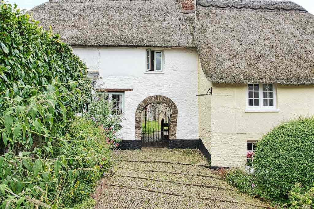 The churchyard entrance is straight through an old thatched cottage