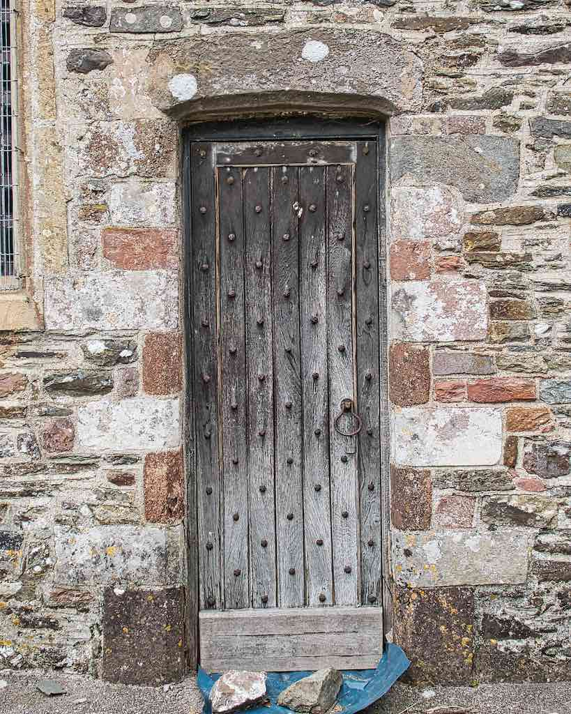 A rough old door with rough old stone and a rough old beauty