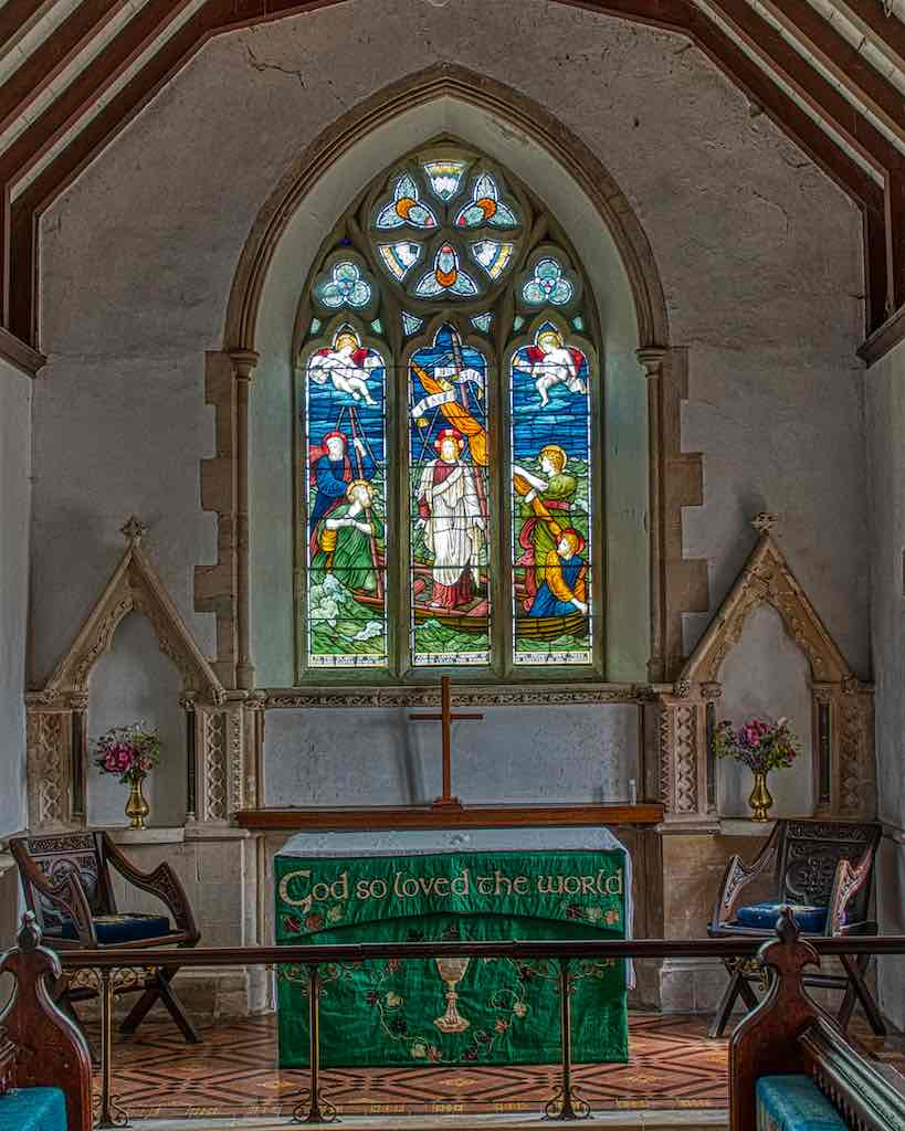 The sanctuary with grand stonework and a powerful window